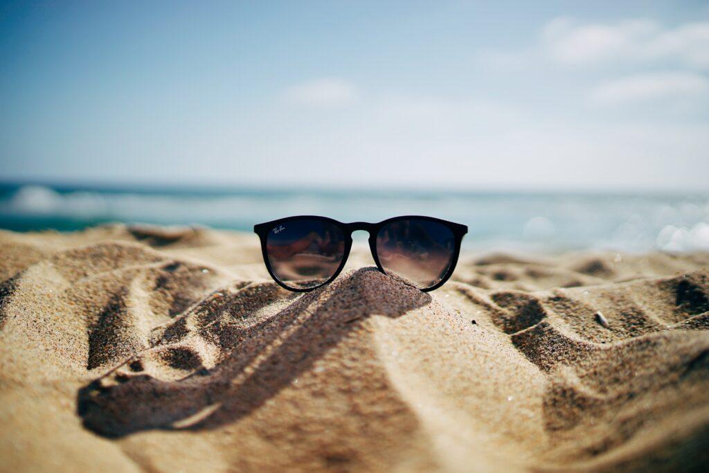black sunglasses on the sand