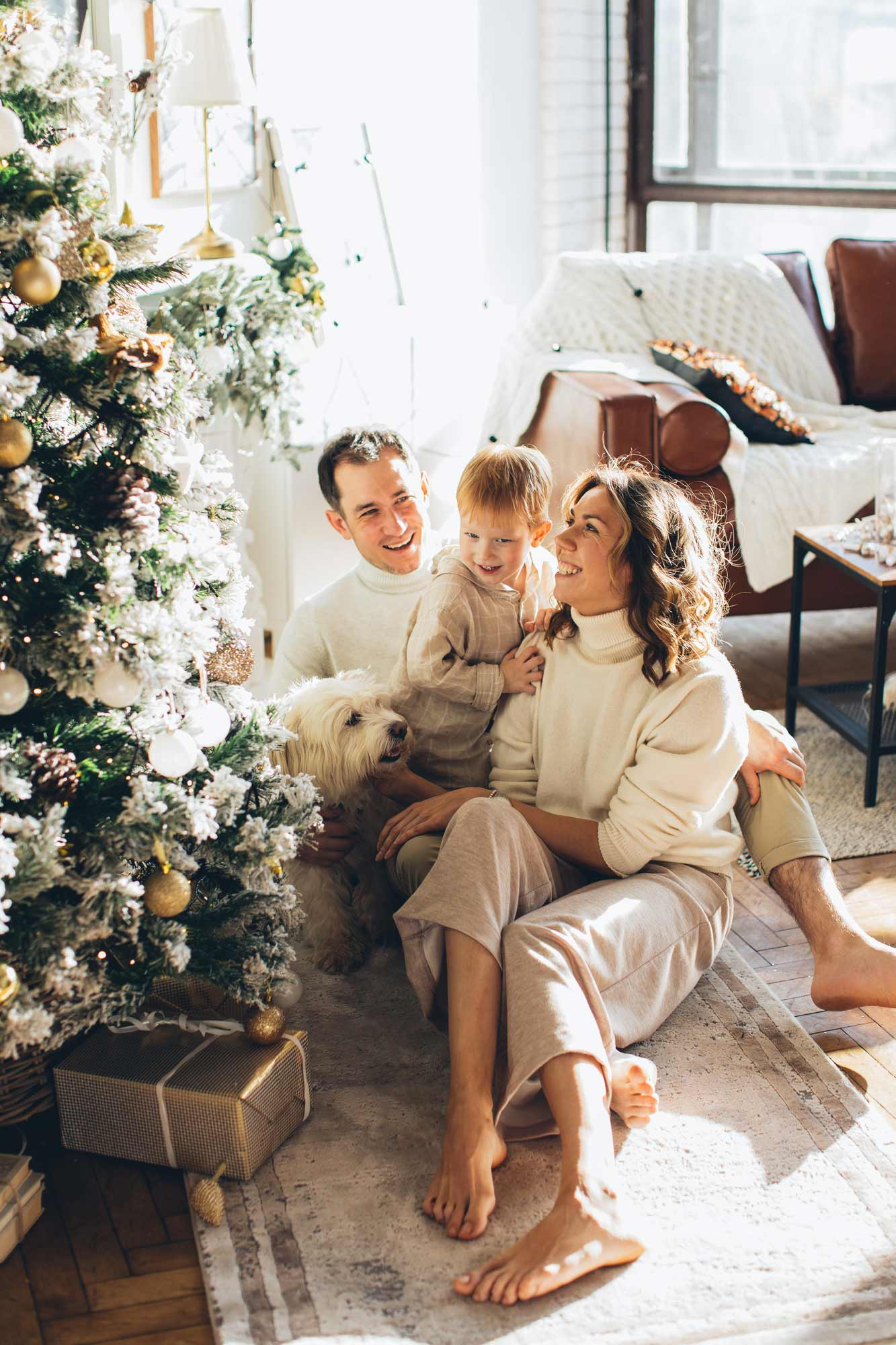 Family sitting beside a Christmas tree