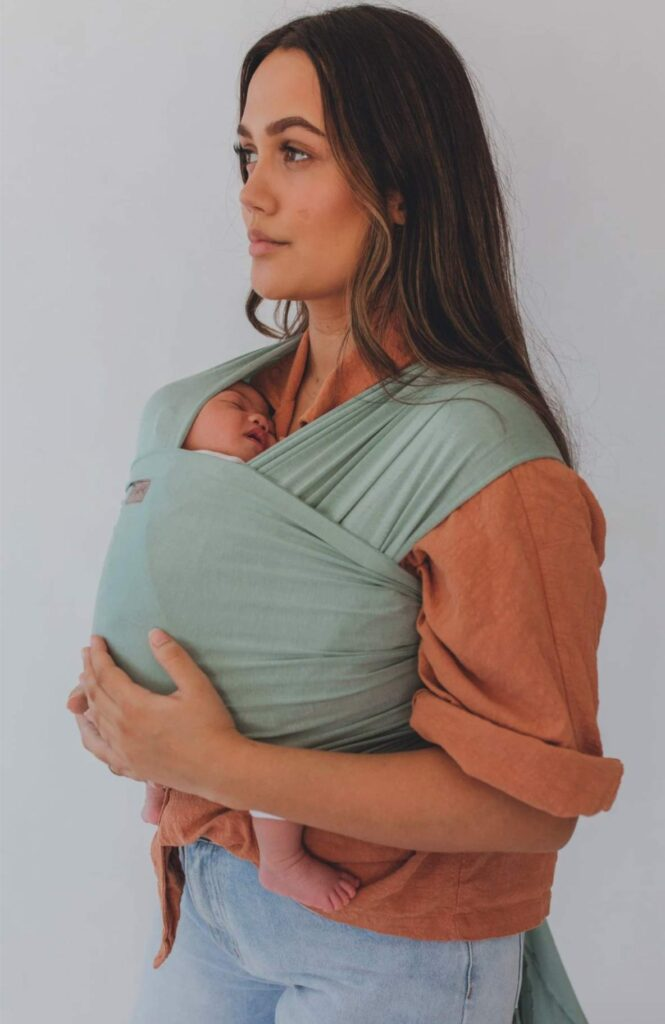 woman holding her wrapped baby
